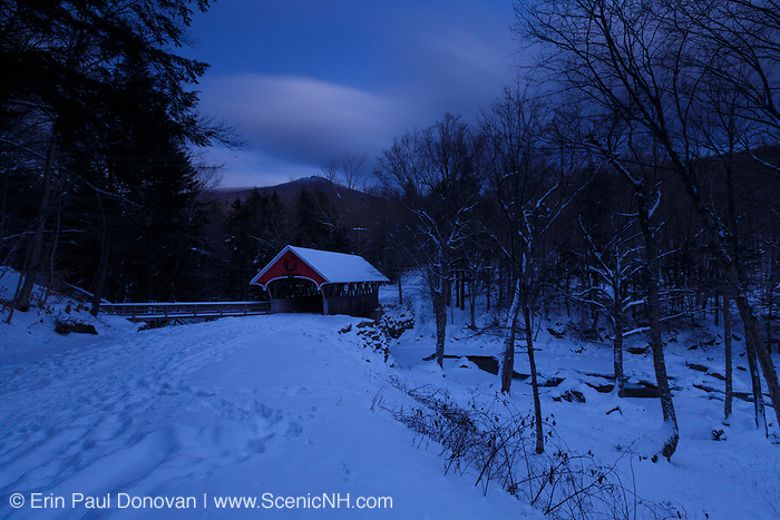 Franconia Notch State Park - Flume Covered Bridge in Lincoln, New Hampshire USA covered in snow during the night.