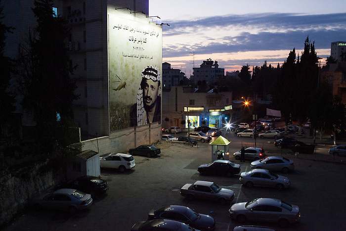 Nov 2012, Ramallah. A parking in the city center, with the image of Yasser Arafat on an advert. The former president has remained an icon in the mind of most Palestinian, for whom he has been the unique legitimate leader for the National cause. However, there is a strong bitterness concerning his strongest achievement, the Oslo agreements, that failed in creating a Palestinian state and instead became the base of the unbalance distribution of power between the Palestinian Authority and Israel.