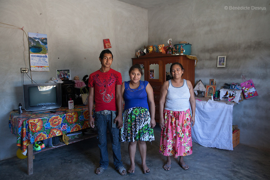 """Xhunaxhi Rosalía Santiago López (C) portrayed with her partner Rolando Luis López (L) and her mother Antonia López Guerra (R) at their home in Santa María Xadani, Oaxaca, Mexico on February 18, 2016. Xhunaxhi – her name means """"virgin"""" in Zapotec – is 14 and lives with her 18-year-old partner and her mother, who had her own first child aged 17, in the town of Santa María Xadani in the southern Mexican state of Oaxaca. Xhunaxhi, who speaks little Spanish, is painfully shy and childlike and punctuates her comments with giggles. She is five months pregnant, but seems not to really understand – she has to ask her mother when her baby is due. She left school at 10 to travel with her family to Tepic, in the western state of Nayarit, for six-month stints working cutting sugar cane. She met her boyfriend last year, keeping the relationship secret from her mother, and was """"stolen"""", according to the Zapotec tradition. She plans to marry legally at 18. While Mexico has outlawed marriage under the age of 18, many young girls become unofficial wives and mothers much earlier. In Juchitán, teenage pregnancy is expected, even prized. Mexico ranks first in teenage pregnancies among the member countries of the Organization for Economic Co-operation and Development(OECD). Photo by Bénédicte Desrus"""