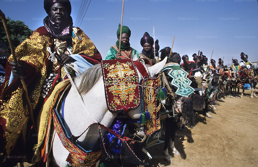 Local chiefs on horses during the Durbar Fantasia..The Durbar Fantasia, is the moment where The Husa residents of Kano wear traditional dress, their local leaders and chiefs mount horses, and together with their militias display allegiance and homage to their leader, the Emir of Kano. This takes place after Ramadan. The Emir is Kano's State official political and economic feudal leader, everyone seeks to be in his pleasure, otherwise they reap the consequences..Kano is the largest Muslim Husa city, under the feudal, political and economic rule of the Emir. Kano and the other eleven northern states are under Islamic Sharia Law which is enforced by official state apparatus including military and police, Islamic schools and education, plus various volunteer Militia groups supported financially and politically by the Emir and other business and political bodies. 70% of the population live below the poverty line. Kano, Kano State, Northern Nigeria, Africa