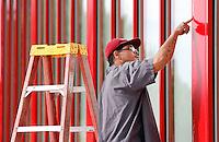 NWA Democrat-Gazette/DAVID GOTTSCHALK  Ronnie Parker, with RGC Glass of Fayetteville, applies a line of caulk Monday, September 14, 2015 at Discount Tires in Fayetteville. Parker mixed a red dye with the silicon caulk before applying for weather proofing.