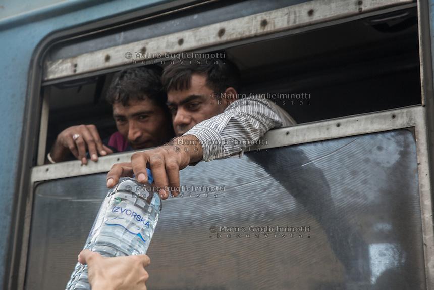 due migranti prendono una bottiglia d'acqua dal finestrino del treno<br /> two migrants take a bottle of water from the train window