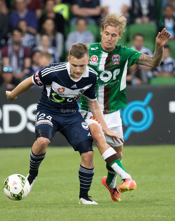 Scott GALLOWAY of the Victory and Jacob PEPPER (16) of the Jetscompete for the ball in round 12 A-League match between Melbourne Victory and Newcastle Jets at AAMI Park in Melbourne, Australia during the 2014/2015 Australian A-League season. Melbourne def Newcastle 1-0