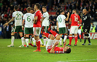 Ireland players (celebrate their win while Sam Vokes of Wales (C) rolls on the ground dejected during the FIFA World Cup Qualifier Group D match between Wales and Republic of Ireland at The Cardiff City Stadium, Wales, UK. Monday 09 October 2017