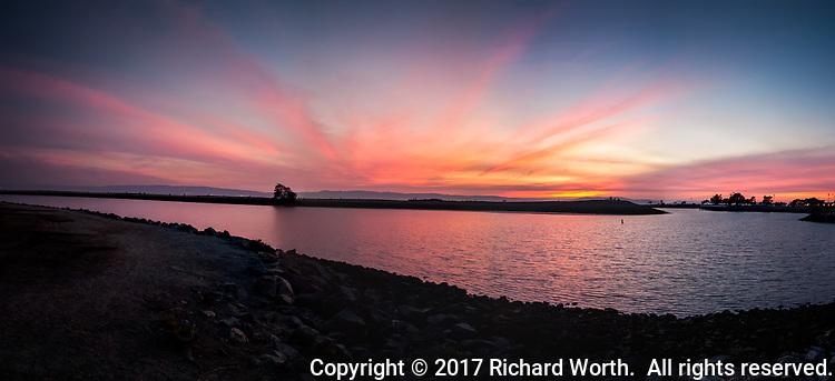 A panoramic view of sunset over the small boat lagoon at the San Leandro Marina Park along San Francisco Bay.