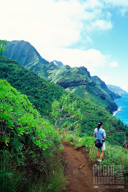 Hiker enjoys coastline views from the Kalalau Trail, an 11-mile trail along the Na Pali Coast, Kauai's remote north shoreline