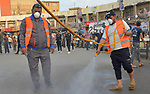 Iraqis workers wearing protective gear, disinfects streets, as a preventive measure amid fears of the spread of the coronavirus COVID-19, in Iraq's southern city of Nasiriyah, on March 16, 2020. For most people, the new coronavirus causes only mild or moderate symptoms. For some it can cause more severe illness. Photo by Wadaa al-Aumry