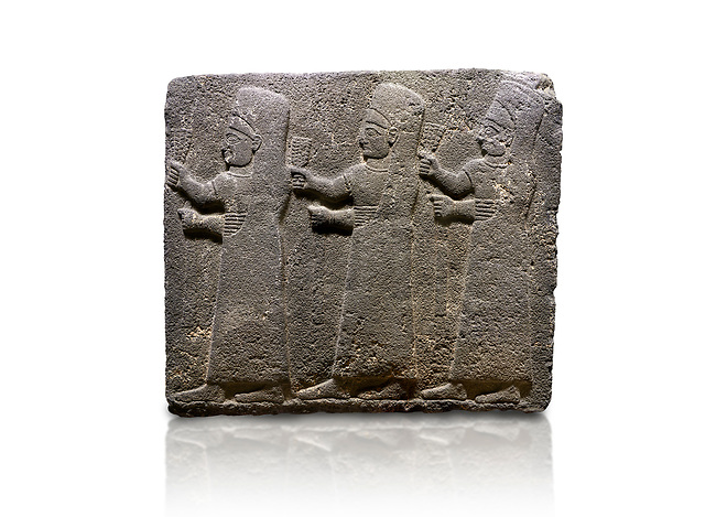 Hittite monumental relief sculpted orthostat stone panel of a Procession Basalt, Kargamis, Gaziantepe, 900 - 700 B.C. Anatolian Civilisations Museum, Ankara, Turkey.<br /> <br /> It is a depiction of three marching female figures in long dress with a high headdress at their head. These women are considered to be the nuns of the Goddess Kubaba. The figures in the front and behind have a bunch of spicy in their right hand while the figure in the middle has an empty right hand. Figures carry objects similar to a sceptre in their left hand. <br /> <br /> Against a white background.