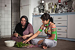 SULAIMANIYAH, IRAQ: Professional cyclist Nyan Yassin helps her mother Mhabad prepare food in the family home.  Women, especially married women, spend a large portion of the day preparing food in Iraq.<br /> <br /> Nyan Yassin, 24, is a professional competitive cyclist in Sulaimaniyah in the semi-autonomous region of Iraqi Kurdistan.  She is the captain of an all-female club called Newroz Club, which is the only cycling club for women in Sulaimaniyah, although there are other clubs around Iraq.  She trains and competes on roads that are badly surfaced and busy with traffic.<br /> <br /> Nyan was the first woman to start cycling in Sulaimaniyah.  She was always competitive and after trying her hand at different sports she settled on cycling.  She is now the top female cyclist in Iraq.  Her nickname is MigMig after the noise made by the cartoon character Roadrunner.<br /> <br /> Despite being clearly talented at her sport Nyan knows that in a couple of years she will have to get married and then abandon it as, in the traditional society that Kurdistan is, being a wife and a competitive sportswoman at the same time is not an option.<br /> <br /> Photo by Gona Hassan/Metrography