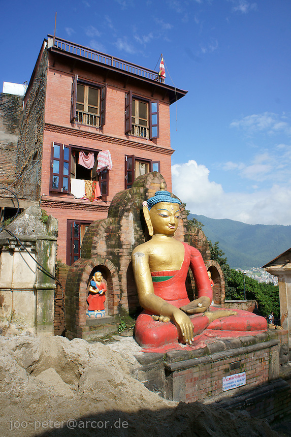 Buddha sculpture in buddhist temple Swayambhu in Kathmandu, Nepal, September 2011, with typical brick-stone building  in background.