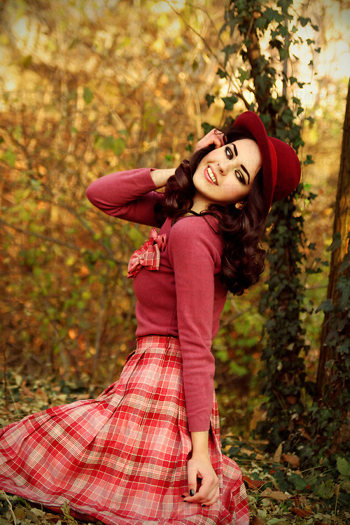 A pretty brunette in pink vintage clothing , wearing a red hat and sitting in a park.