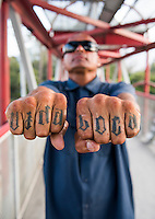 """Vida Loca"" (crazy life) tattoo. Jesus Aleman from the ""13"" gang earns a living by blowing fire at the traffic lights. Monterrey, Nuevo Leon, Mexico"