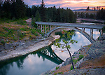 Idaho, North,Post Falls. The historic WWP arched bridge over the North Channel of the Spokane River at sunset.