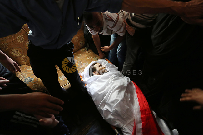 Relatives of Palestinian Ahmed Qutoosh, 23, who died of his wounds endured during clashes with Israeli troops in a tent city protest where Palestinians demand the right to return to their homeland at the Israel-Gaza border, mourn over his body during his funeral in Nuseirat, in the central Gaza Strip, on May 25, 2018. Photo by Ashraf Amra
