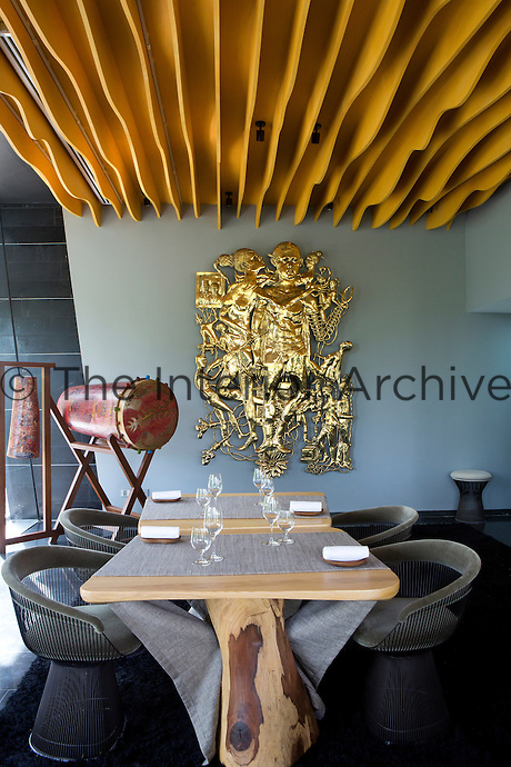 Natural wood tables are teamed with armchairs by Warren Platner in the dining area