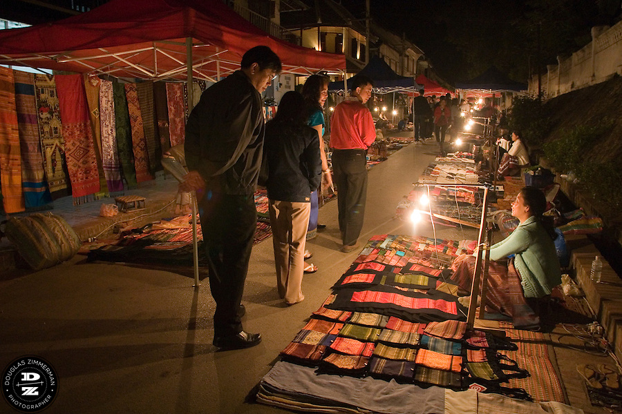 Tourists view local goods available for sale in a night market in Luang Prabang, Laos. Photograph by Douglas ZImmerman