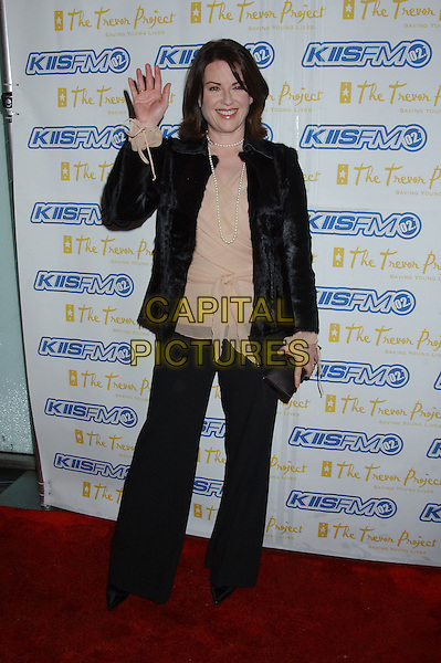 MEGAN MULLALLY.The Trevor Project's 'Cracked XMAS 7' held at the Wiltern LG..December 5th, 2004.full length, waving gesture, black trousers, black fur jacket, beige, top, pearls.www.capitalpictures.com.sales@capitalpictures.com.© Capital Pictures.