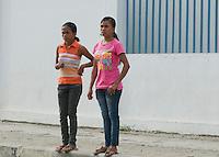 Two girls wait to cross a busy street in Dili, Timor-Leste (East Timor)