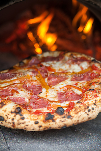 Freshly cooked pizza coming out of a wood burning oven, with flames visible in background.. Blistered crust, and topped with mozzarella cheese, red peppers, tomato sauce, and salami.