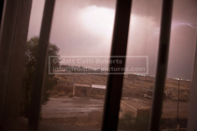 28/09/2014. Al-Yarubiyah, Syria. Lightening illuminates the border town of Al-Yarubiyah, Syria, during a sandstorm.<br /> <br /> Facing each other across the Iraq-Syria border, the towns of Al-Yarubiyah, Syria, and Rabia, Iraq, were taken by Islamic State insurgents in August 2014. Since then The town of Al-Yarubiyah and parts of Rabia have been re-taken by fighters from the Syrian Kurdish YPG. At present the situation in the towns is static, but with large exchanges of sniper and heavy machine gun fire as well as mortars and rocket propelled grenades, recently occasional close quarter fighting has taken place as either side tests the defences of the other.