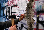West Berlin, West Germany<br /> November 14, 1989 <br /> <br /> An unidentified man uses a chisel to break the Berlin Wall. Germans gathered as the wall is dismantled and the East German government lifts travel and emigration restrictions to the West on November 9, 1989.