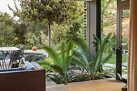 Open air living room connected to patio through sliding glass doors; Coyote House, SITES® residential home with sustainable garden; Santa Barbara California, Susan Van Atta design