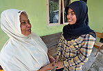 Nurul Aina (right) talks with her grandmother in Banda Aceh, Indonesia. Aina was just 8 years old in 2004 when a massive tsunami swept over the city, killing her parents and two siblings and leveling their home. Aina was fortunately visiting relatives in a neighborhood far from the seashore when the tsunami hit. With assistance from the Katahati Institute and Diakonie Katastrophenhilfe, a new house was built and titled in Aina's name, an accomplishment that required considerable legal advocacy by Katahati staff. As a result, rental income from the house has paid for Aina's schooling while she lives with her grandmother. Now 18, Aina is studying English at a local university, and plans to move into her house some day. The tsunami killed 221,000 people in Aceh province and left more than 500,000 displaced.
