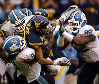 West Virginia quarterback Pat White (5) is tackled by a group of North Carolina defenders during the Meineke Car Care Bowl college football game at Bank of America Stadium in Charlotte, NC.