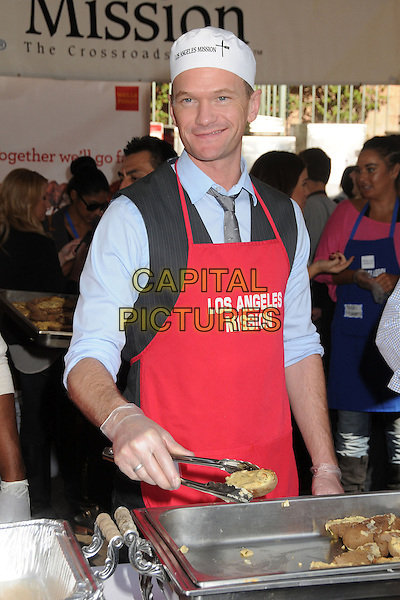 Neil Patrick Harris.Los Angeles Mission Thanksgiving Dinner 2012 held at the LA Mission, Los Angeles, California, USA..November 21st, 2012.half length red apron blue gloves shirt white hat  tongs food.CAP/ADM/BP.©Byron Purvis/AdMedia/Capital Pictures.