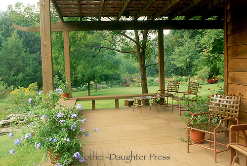 Inviting deck on home with chairs and plants opening onto garden and yard, midwest USA