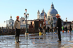 Gondola skipper at St Mark's square during an acqua alta (high-water). The Acqua Alta, a convergence of high tides and a strong sirocco, reached 125 centimetres in Venice, on November 20, 2013.  <br /> <br /> &copy; Pierre Teyssot