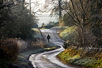 Women walks in a frost covered country lane, Swinbrook, The Cotswolds, Oxfordshire, United Kingdom