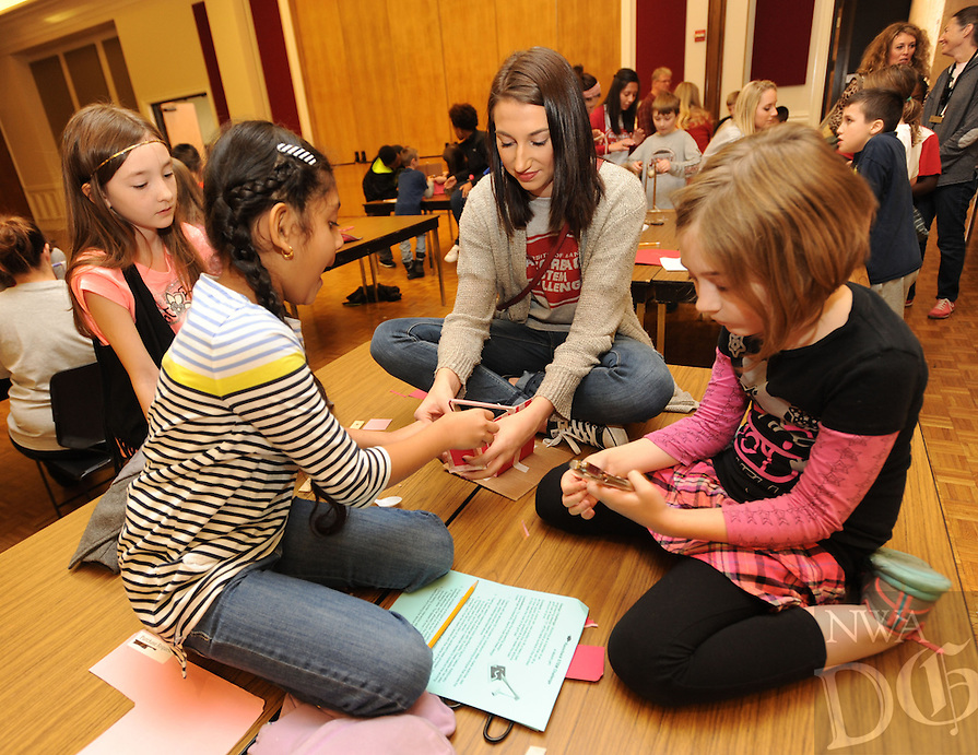 NWA Democrat-Gazette/ANDY SHUPE<br /> Ashlyn Garton (center) a University of Arkansas junior, helps Emma Sumner, 8, (from left) Aasritha Jayanthi, 8, and Makayla Defoor, 9, Friday, Dec. 11, 2015, as they make a crane to lift a golf ball while participating in the Razorback STEM Challenge sponsored by the University of Arkansas. Third- and fourth-grade students from Leverett Elementary School in Fayetteville participated in the event which challenged students to construct machines with everyday items to complete tasks.