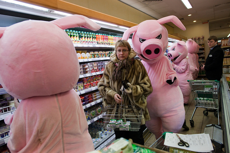 Moscow, Russia, 03/03/2011..A shopper surrounded by demonstrators in a pig costumes as members of health campaign group Pigs Against check the sell-by dates and quality of food in a city centre supermarket while dressed as pigs.
