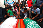Palestinian mourners at a mosque gather around the bodies of Mousa Abu Muamer, 56, and his son, Saddam, 27, who were killed in an overnight Israeli missile strike at their house in the outskirts of the town of Khan Younis, southern Gaza Strip, Monday, July 14, 2014. Saddam's wife Hanadi, 27, was also killed in the attack. Photo by Ramadan El-Agha