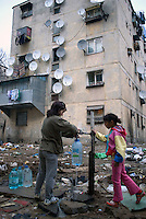 ROMANIA, 12.2006; Bucharest..Children filling bottles with drinking water, Muntii Carpati area, Bucharest, Romania..© Egyed Ufo Zoltan / Est&Ost Photography