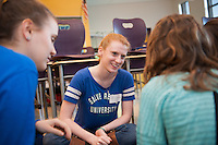 Salve Regina volunteers Cathryn Blair,'18, center, and Genna Hoyt,'18, left, help students with their language skills at the Pell School in Newport.
