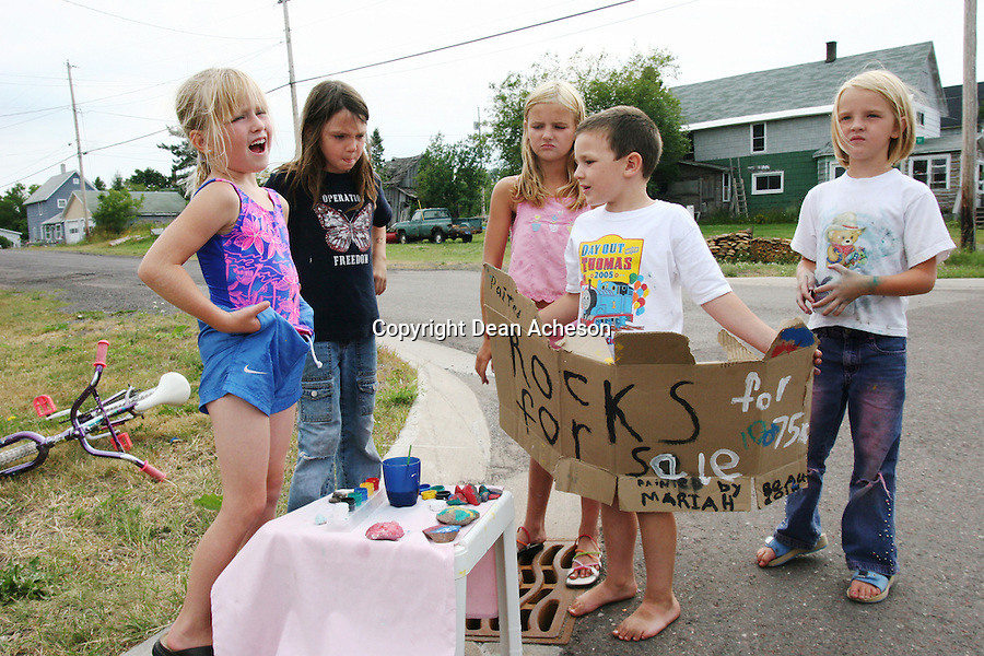 Neighborhood children discuss the day's profit and loss picture from selling painted rocks at their stand set up at an intersection in Calumet, Mich. Some of the profit literally went down the drain after dropping a couple of quarters in the storm water catch basin underfoot.