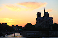 The back of the church of Notre Dame within its isle in Paris, in the light of an artistic sunset. Digitally Improved Photo.
