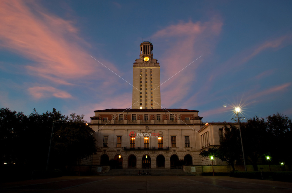 Pink sunset falls on the university campus clock tower and main building, Austin, Texas, USA.