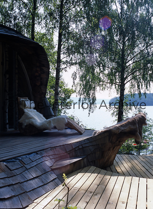 An animal-skin clad sun-lounger on the terrace with a view through the tall birch trees to the lake