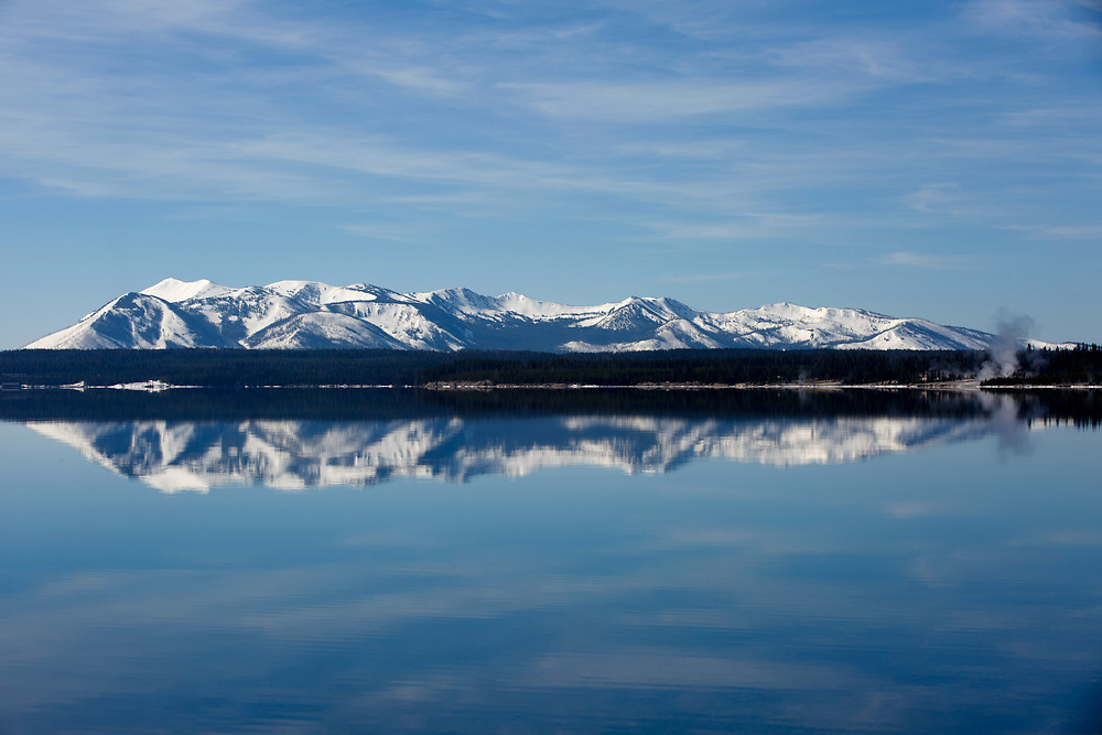 Steam from the West Thumb Geyser Basin, right, and mountains including Mount Sheridan (10,298 feet) are reflected in Yellowstone Lake in Yellowstone National Park, Wyoming on Tuesday, May 23, 2017. (Photo by James Brosher)