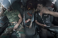 Opposition fighters sit inside a truck as they get back from the frontline battles to the FSA head quarters in Tarik Albab neighborhod in north of Aleppo City.