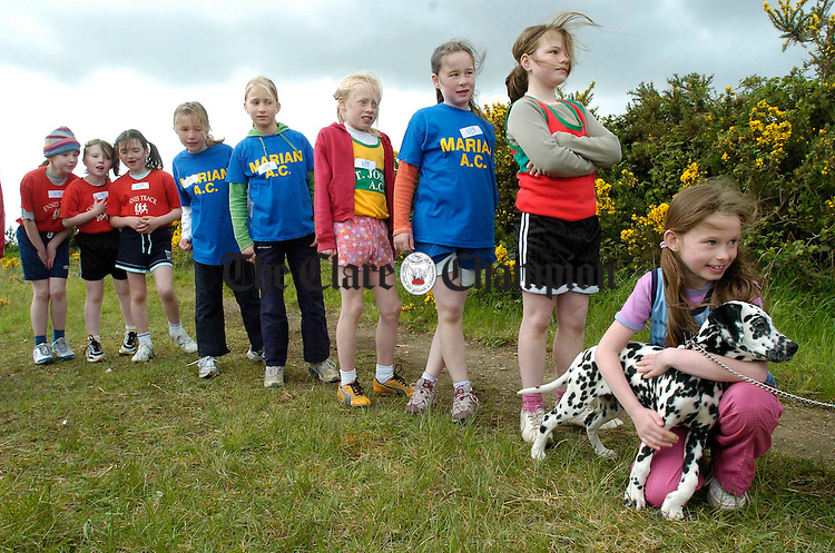 """Fiona Brew of Tullycrine takes time to cuddle """"Honey"""" as she lines up with other competitors for the long jump during the Clare Juvenile Athletics championships in Mullagh. Photograph by John Kelly."""