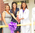 Actress Sandra Bullock cuts the ribbon at the Warren Easton Charter School Health Clinic Sunday Aug. 29th 2010 on the 5th anniversary of Hurricane Katrina. Bullock is joined by the school nurse whose dream it was to open the health clinic on right, Cassondra Ferrand, Warren Easton Charter School Nurse and the school principal  Alexina Medley to cut the ribbon at the new Health Center. PHOTO©SuziAltman