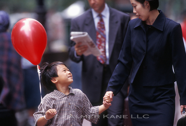 Asian businesswoman walking with her son on a city street