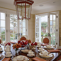 An antique octagonal table laid for dinner under an 18th century-style lantern in the bright and airy garden dining room