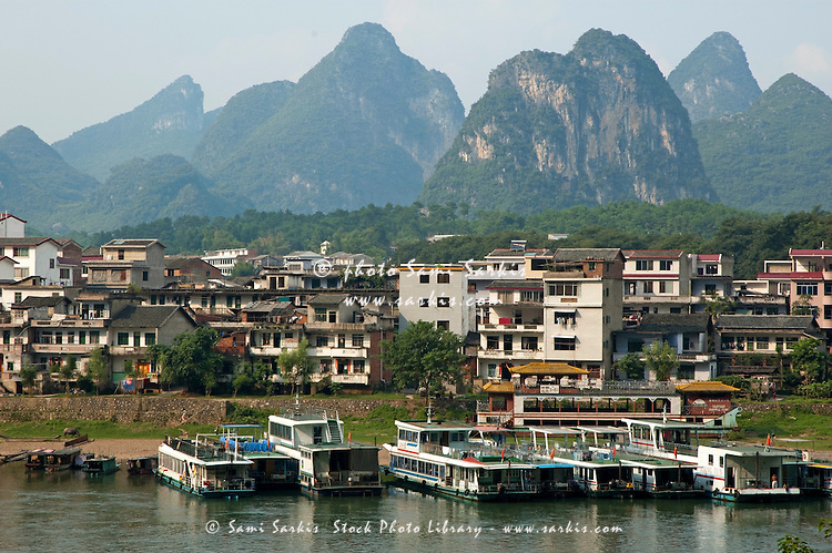 Apartment buildings of a village on Li Jiang River at sunset, Yangshuo, Guangxi, China.