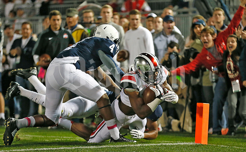 Ohio State Buckeyes running back Ezekiel Elliott (15) scores a touchdown as Penn State Nittany Lions safety Adrian Amos (4) attempts a tackle at Beaver Stadium on October 25, 2014.  (Chris Russell/Dispatch Photo)
