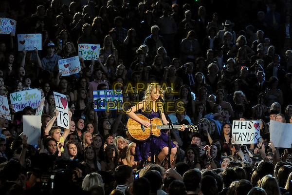 TAYLOR SWIFT .performs during the 43rd Annual CMA Awards, Country Music's Biggest Night, held at the Sommet Center, Nashville, Tennessee, USA, 11th November 2009. live show on stage half length performing concert music gig guitar crowd audience purple microphone signs banners  playing .CAP/ADM/LF.©Laura Farr/AdMedia/Capital Pictures.